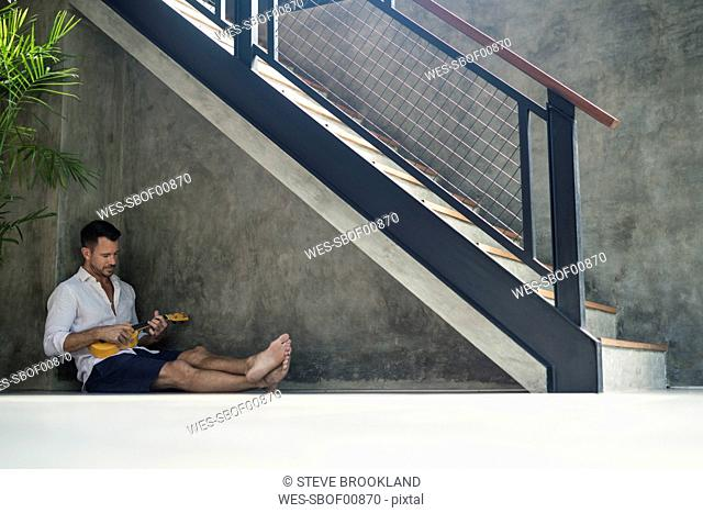 Mature man sitting under staircase, playing the ukulele