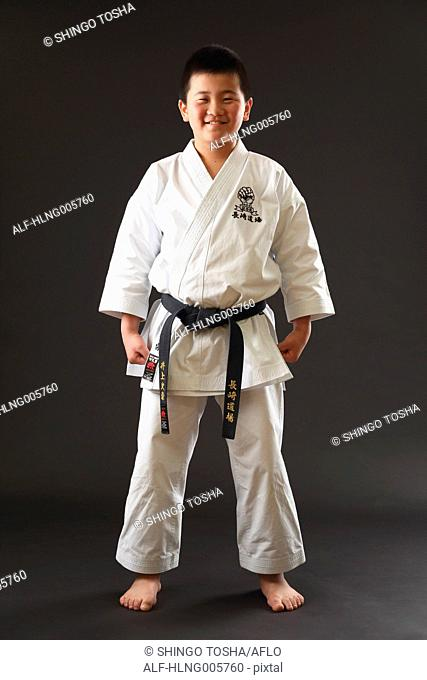 Japanese kid in karate uniform on black background
