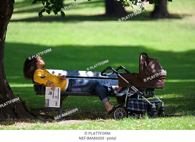 Young man with baby carriage relaxing on bench in park