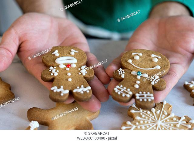 Man's hands holding two different Gingerbread Men, close-up