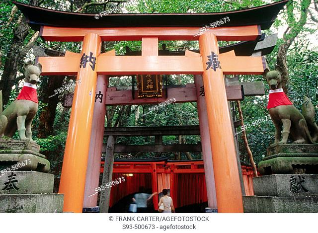 A view of the many Tori gates that line the mountain pathway at Fushimi-Inari Shrine, with two messenger foxes. Fushimi-Inari. Kyoto. Japan