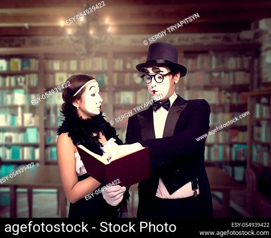 Two pantomime theater performers posing with book. Mime actor and actress performing