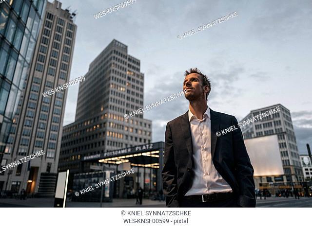 Germany, Berlin, smiling businessman at Potsdamer Platz in the evening