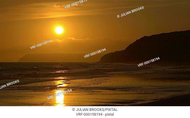 The sun setting behind a sandy beach, Isle of Wight