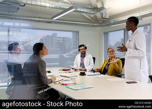 Female doctor leading conference room meeting