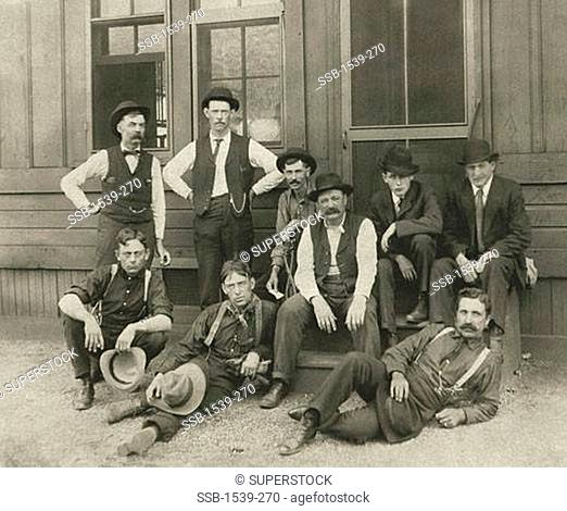 Group of men posing in front of a railroad depot, USA, 1914