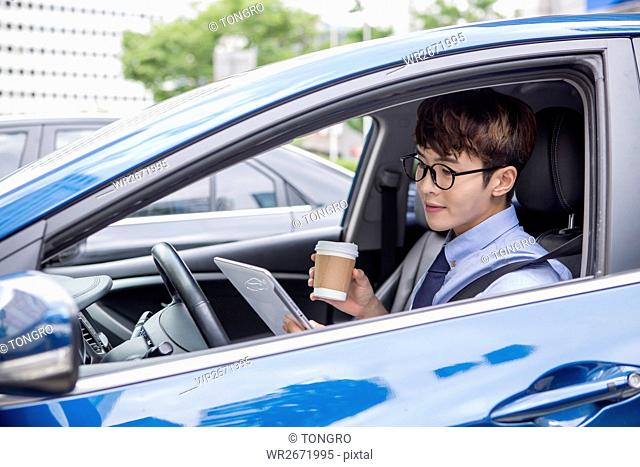 Businessman with takeout coffee in his car