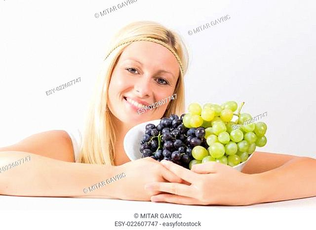 Attractive blonde woman holding grapes