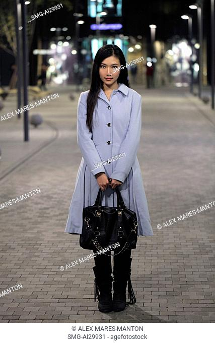 Young woman standing on the street holding her purse, at night