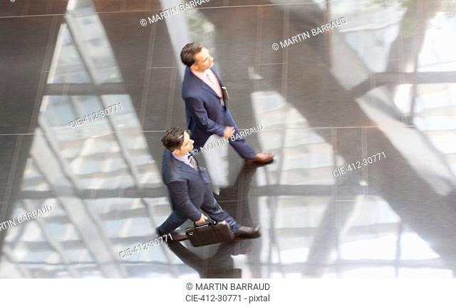 Corporate businessmen walking in modern office lobby