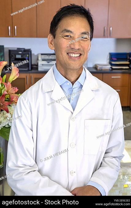 Asian male doctor standing inside his office