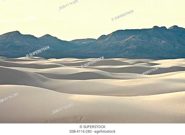 USA, New Mexico, White Sands National Monument, Sand dunes and mountains at sunset