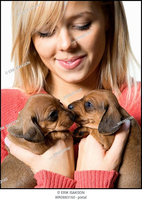 Close-up of a young woman holding two puppies
