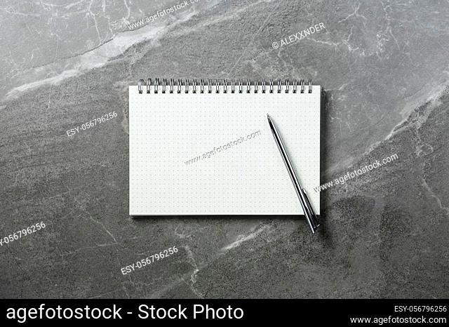 open notebook with pen on marble top view, school notepad on a dark table, office desk flat lay