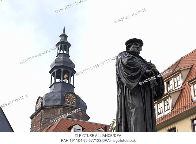 24 October 2019, Eisleben: 23.10.2019, Saxony-Anhalt, Eisleben: View of the gable of the town hall and the Luther monument in Eisleben. (l.-r