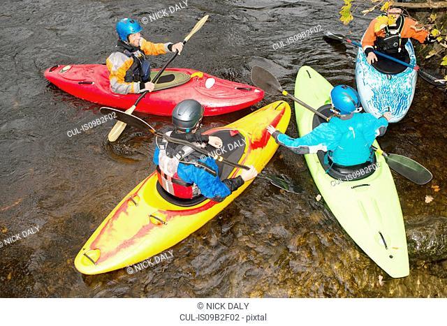 Overhead view of kayak team talking on river Dee