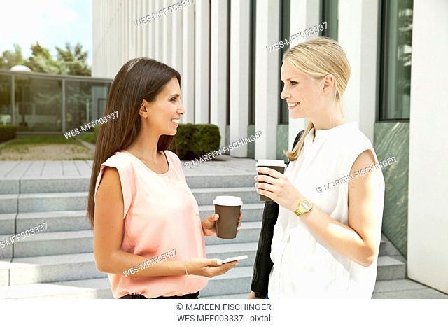 Two businesswomen talking outside during a coffee break