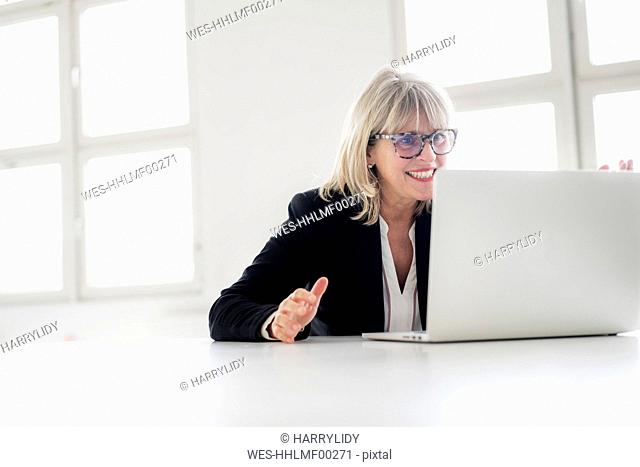 Smiling mature businesswoman working on laptop at desk in the office