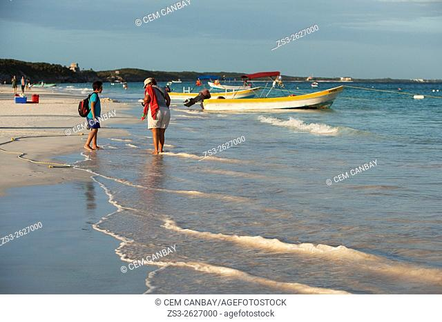 Tourists walking at the beach near the fishing boats, Tulum, Quintana Roo, Yucatan Province, Mexico, Central America