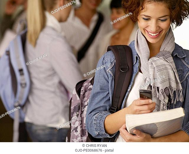 Female college student holding book and checking cell phone