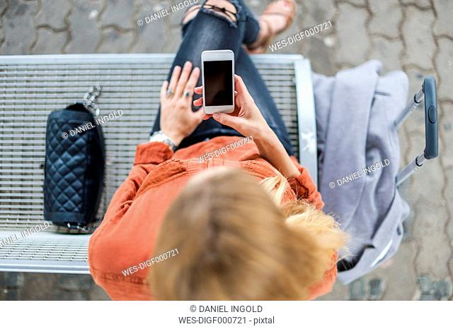 Young woman sitting on bench at platform looking at cell phone