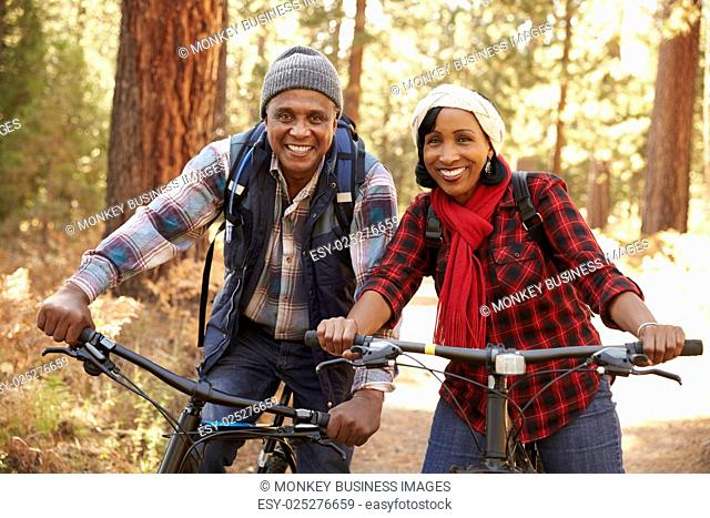 Portrait Of Senior Couple Cycling In Fall Woodland