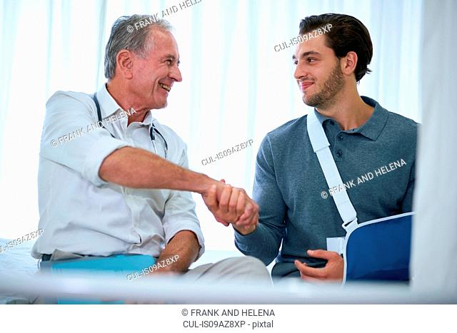 Doctor shaking hands with man in arm sling