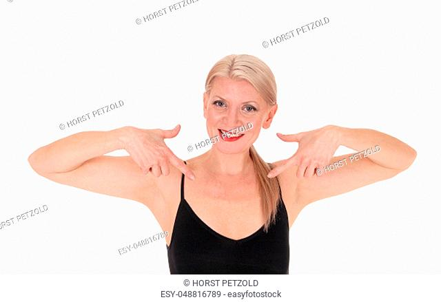 A close up image of a smiling blond woman in a black top pointing.with booths hands at herself, isolated for white background