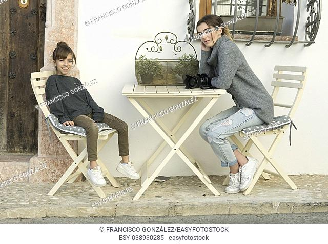 Two sisters sitting at the door of a hotel in the beautiful town of Altea, in the province of Alicante in Spain