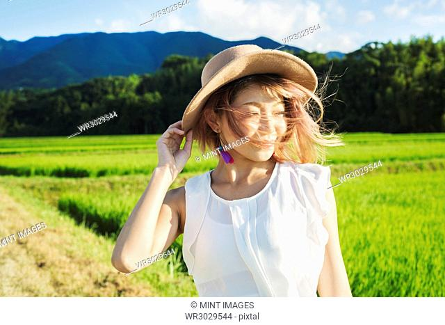 A young woman holding her hat in the wind, by rice paddy fields of green shoots, and mountain landscape