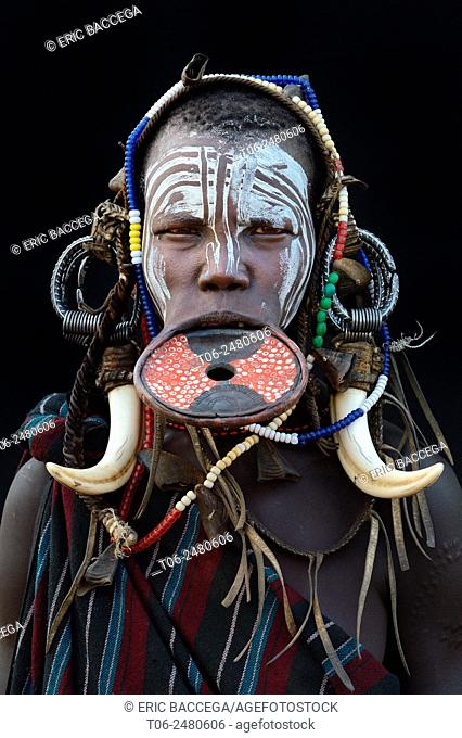 Portrait of woman of the Mursi tribe traditionally decorated and painted, wearing a large clay lipplate, Omo Valley, Ethiopia, Africa