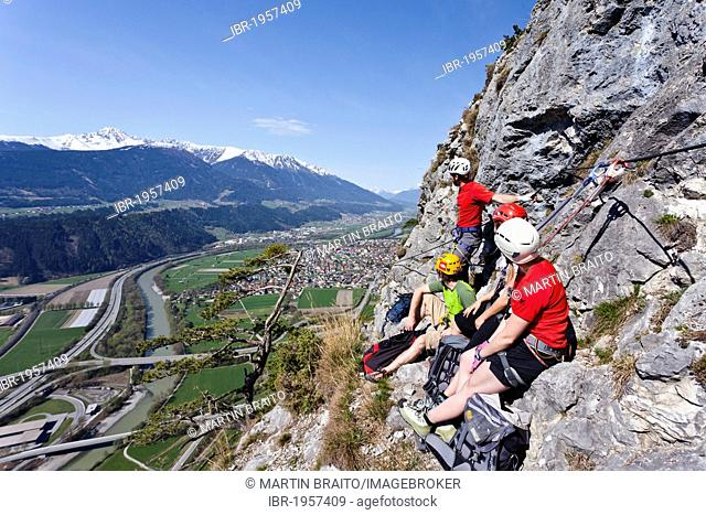 Mountain climbers ascending the Kaiser Max climbing route on Martinswand near Innsbruck, looking over the Inntal Valley and Zirl, North Tyrol, Tyrol, Italy