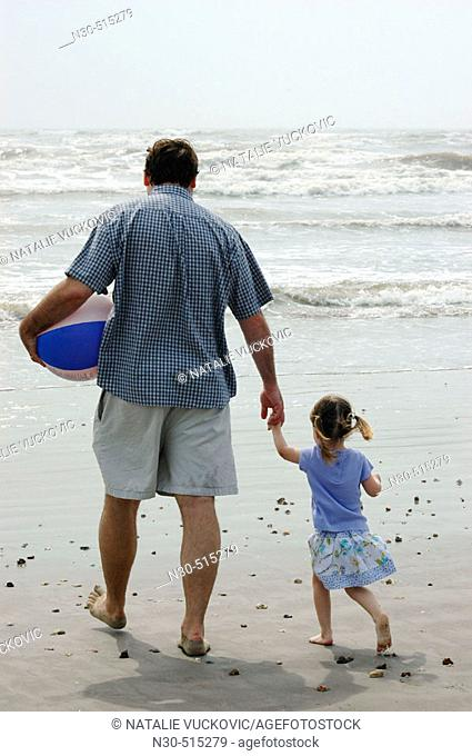 Rear view of father and daughter walking on beach