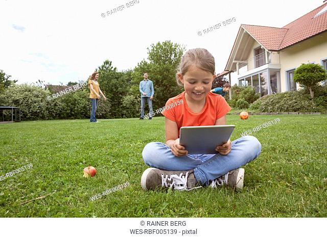 Smiling girl sitting in garden using tablet with family in background
