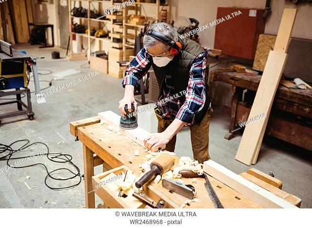 Carpenter sanding down a plank of wood in carpentry