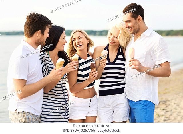 happy friends eating ice cream on beach