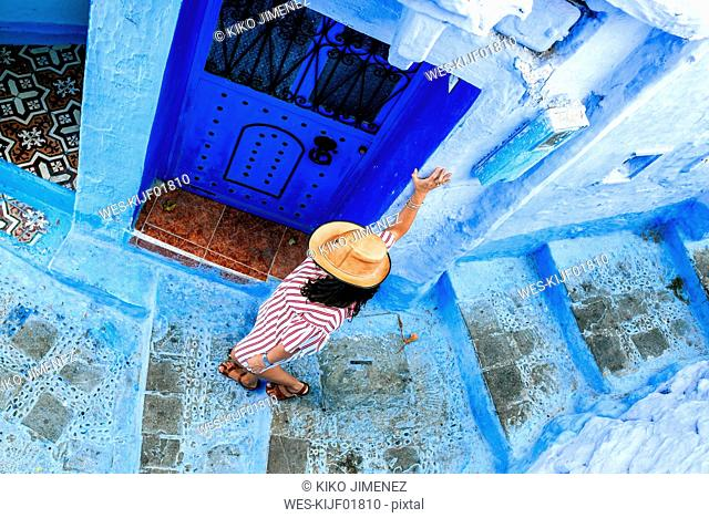 Morocco, Chefchaouen, woman walking alley downwards, top view