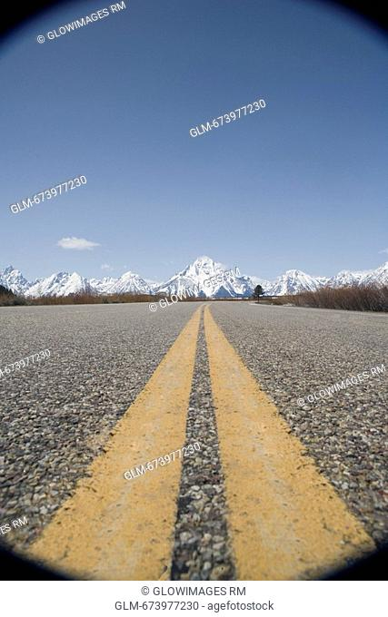 Dividing lines on a road with mountains in the background, Grand Teton National Park, Wyoming, USA
