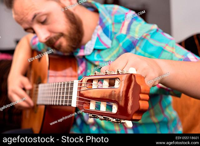 Bearded hipster man hand adjusting acoustic guitar. Close-up selective focus on hand