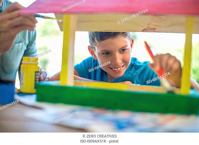 Father and son doing crafts together, painting wooden birdhouse