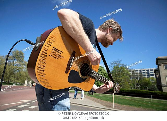 Busking musician with amplified acoustic guitar list of places visited