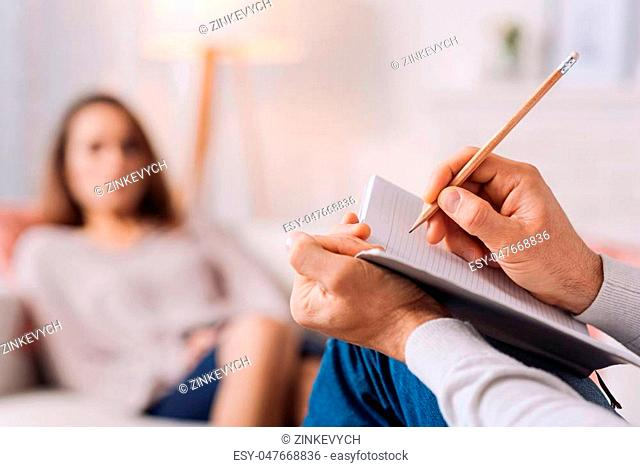 Pay attention to details. Selectife focus of pencil in hands of professional psychotherapist holding it and making notes while talkign with his client