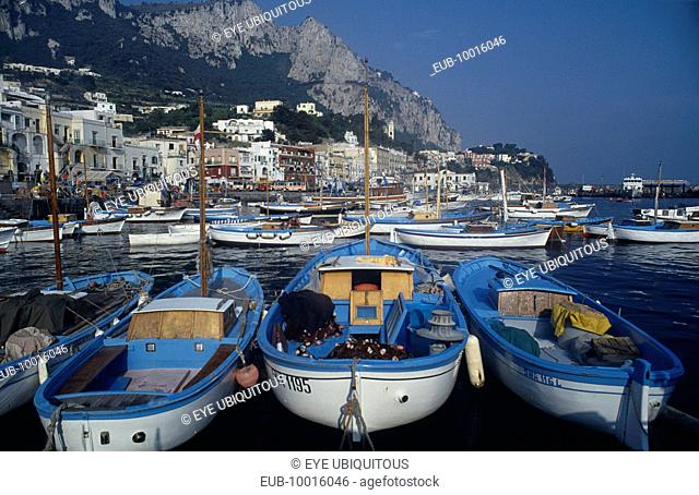 Marina Grande. Moored boats on water with waterside buildings overlooked by mountains