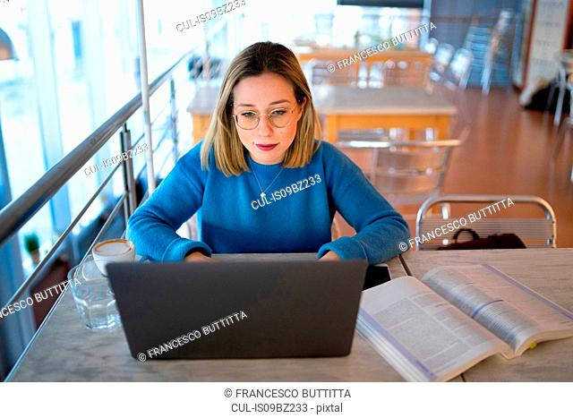 Female higher education student typing on laptop in university cafe