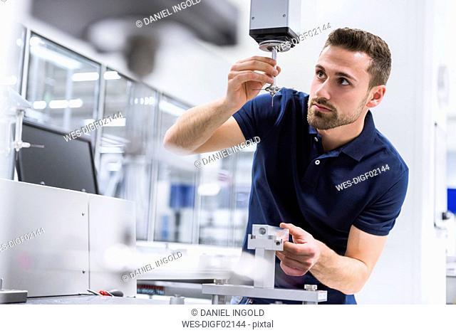 Man adjusting machine in testing instrument room