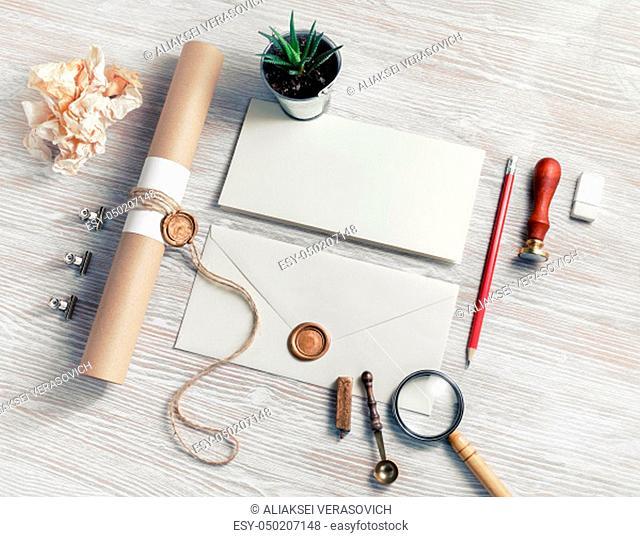 Blank envelope and vintage stationery set on light wood table background. Responsive design mockup