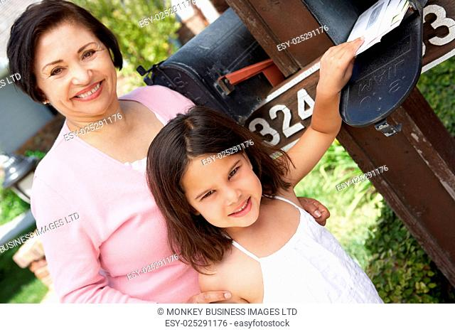 Hispanic Grandmother And Granddaughter Checking Mailbox