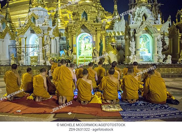 A group of monks pray at one of the shrines at the Shwedagon Pagoda