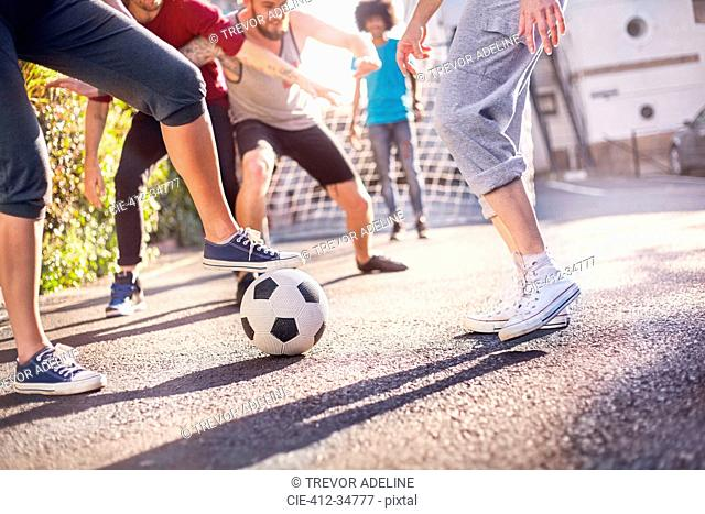 Friends playing soccer in summer street