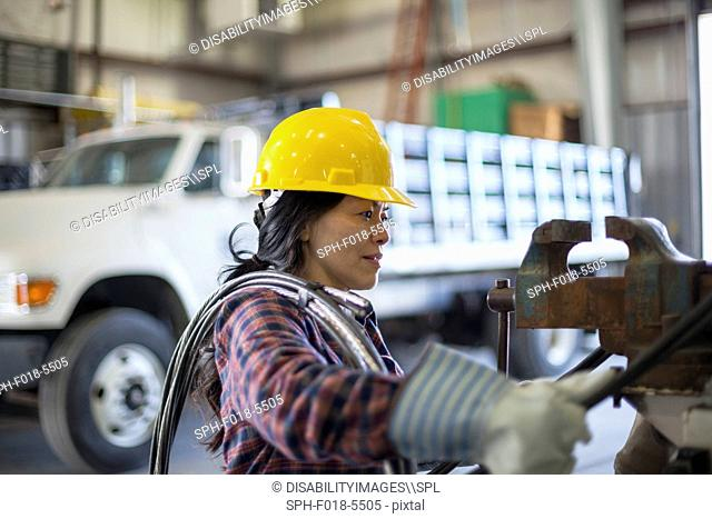 Female power engineer with power cable in service garage